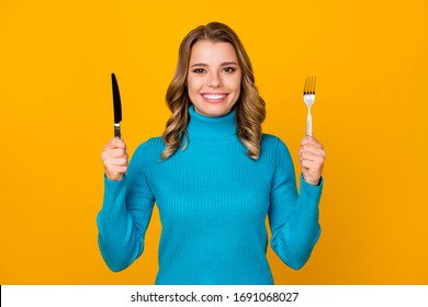 Im starving. Photo of attractive charming wavy lady hold metal knife fork ready to start tasty food dinner meal wear blue turtleneck isolated bright yellow color background