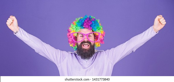 Im a winner. Bearded man celebrating victory in clown wig hairstyle. Man in fashion wig with happy winning gesture. Hipster man wearing rainbow wig hair. Happy man with long beard and curl wig.
