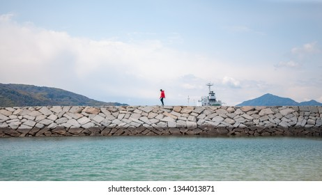 IMABARI, JAPAN - MARCH 27, 2017 : A lone man in red top walking on a stone pier seen from Hakata Island while on the Shimanami Kaido cycling tour starting from Onomichi and ending at Imabari.