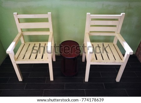 Image Of 2 Identical White Wooden Chair With Brown Small Coffee Table In Between At A