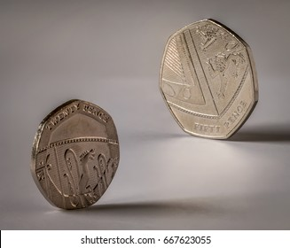 Image of 20 pence & 50 pence British coins, standing upright on their edges. 7 Sided, or Polygon coins. Photographed on a plain white background.