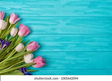 春の背景!木製の背景にチューリップの花束。バレンタインデー、女性の日、母の日、イースターのホリデーグリーティングカード!