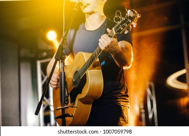歌手はアコースティックギターを演奏し、コンサートで歌う