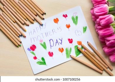 """Kleiner Junge malt Grußkarte für Mutter am Muttertag mit der Aufschrift """"Glücklicher Muttertag"""". Draufsicht"""
