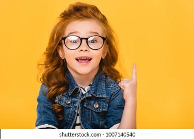 Retrato de niño sonriente en anteojos apuntando hacia arriba aislado en amarillo
