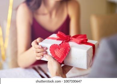 バレンタインデーのコンセプト。と恋に幸せなカップル。レストランでバレンタインデーを祝う若い愛情のあるカップル。恋人たちはお互いに贈り物をします。バレンタインデーのロマンスレストラン-コンセプト