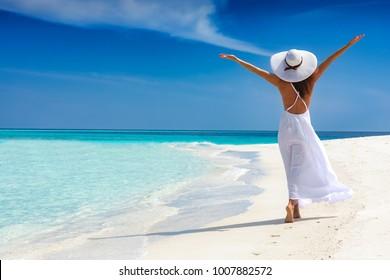 白いドレスを着た幸せな旅行者の女性は彼女の熱帯のビーチでの休暇を楽しんでいます