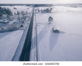 Landschaft am verschneiten Wintertag. Luftaufnahme des ländlichen Dorfes und der Straße im Winter. Finnland