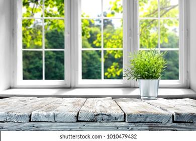 Schreibtisch mit freiem Platz mit grüner Pflanze und Fenster der Frühlingszeit