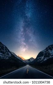 Eine Straße, die in einem Gebirgstal mit Milchstraße im Hintergrund zur Entfernung führt.