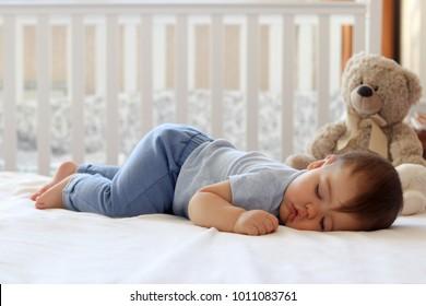 自宅のベッドで彼の胃で寝ている面白い赤ちゃん。子供の昼間のボトムアップの睡眠位置