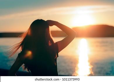 海に沈む夕日を眺める幸せな希望に満ちた女性。地平線に希望を持って見ている夢想家の女の子のシルエット