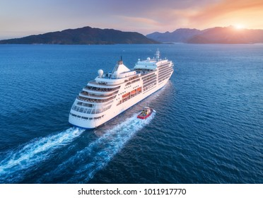 Cruise ship at harbor. Aerial view of beautiful large white ship at sunset. Colorful landscape with boats in marina bay, sea, colorful sky. Top view from drone of yacht. Luxury cruise. Floating liner