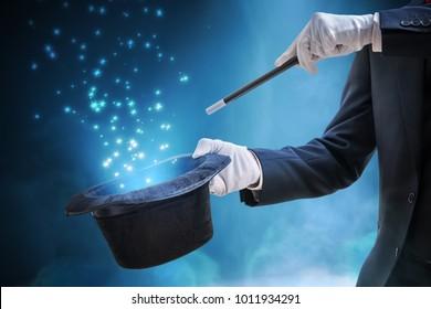 Magier oder Illusionist zeigt Zaubertrick. Blaues Bühnenlicht im Hintergrund.