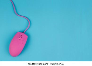 Mouse de computadora rosa sobre fondo azul, espacio de copia