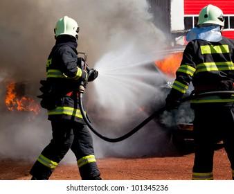 消防士は爆発した燃えている車を消している