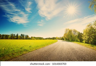 晴れた春の日に田舎のアスファルト道路のパノラマ。太陽、青い空、緑の草、タンポポの美しい自然の風景のルート