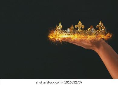 Frauenhand, die eine brennende Krone über schwarzem Hintergrund hält