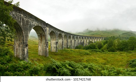 Hochauflösendes Panorama des Eisenbahnviadukts von Glenfinnan (Ort aus dem Harry-Potter-Film), aufgenommen von der Seite, an einem bewölkten Tag mit grauem Himmel und viel grünem Gras und Bäumen. Inverness, Schottland