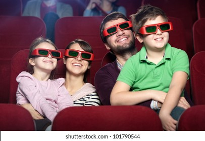 Smiling family in the 3D movie theater