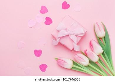 Flores de primavera y caja de regalo o presente en la vista superior de la mesa de color rosa pastel. Tarjeta de felicitación para el día de la mujer o la madre. Endecha plana.