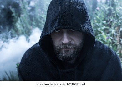 Hooded man wearing a cloak in a mysterious fantasy forest setting.