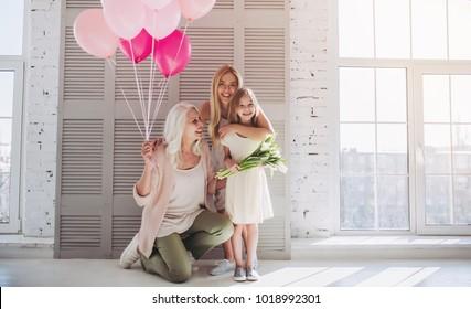 Kleines süßes Mädchen, ihre attraktive junge Mutter und charmante Großmutter stehen mit Luftballons und Blumen im hellen Raum. Frauengeneration. Internationaler Frauentag. Schönen Muttertag.