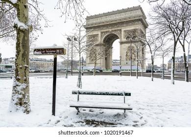 Winter in Paris im Schnee. Der Arc de Triomphe mit einer schneebedeckten öffentlichen Bank im Vordergrund.
