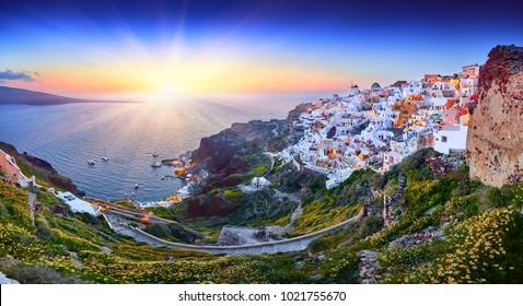 Fira Stadt auf Santorini Insel, Griechenland. Unglaublich romantischer Sonnenuntergang. Oia Dorf im Morgenlicht. Erstaunliche Sonnenuntergangsansicht mit weißen Häusern. Inselliebhaber. Panorama der Bucht. Santorini Blumen.