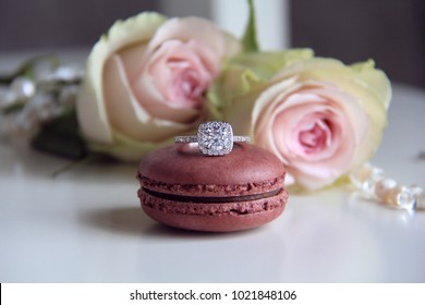 diamond ring on macaron and roses background
