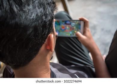 Fokus junger Spieler, der Handyspiel spielt.