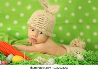 イースターバニーの耳とカラフルな卵を持つ幸せな赤ちゃん-ハッピーイーター
