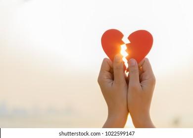 Frauenhand, die gebrochenes rotes Papierherz auf Sonnenuntergang hält. Liebes-, Hochzeits- und Valentinstagkonzept.