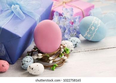 イースター装飾巣、イースター色の卵、ギフト用の箱、白い木製の背景の春の花。グリーティングカードテンプレート