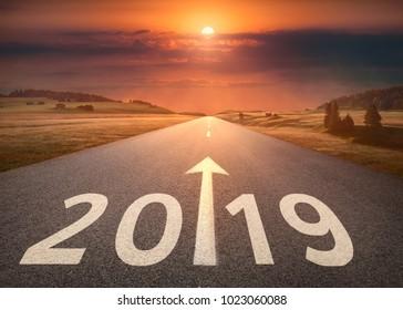 Fahren Sie auf idyllischer offener Straße gegen die untergehende Sonne bis ins neue Jahr 2019. Konzept für Erfolg und Zukunft.