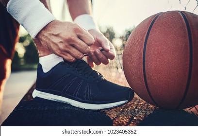 Basketballspieler, der Sportschuhe bindet. Sport, Erholungskonzept