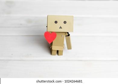 Weinig robotkarakter Danbo die zich op houten vloer met rood in hand hart bevindt
