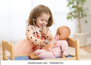 Cute child in kindergarten. Kid in nursery school. Little girl preschooler playing doctor with doll.