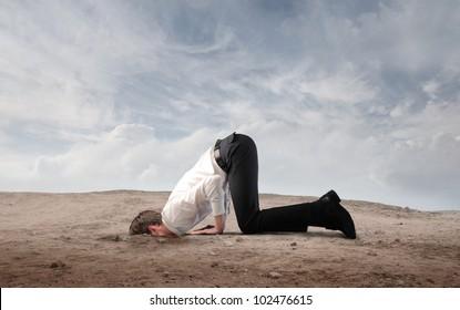 Joven empresario enterrando su cabeza en la arena