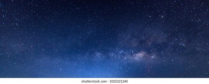 パノラマの青い夜空の天の川と暗い背景の星。ノイズと粒子があります。長時間露光で写真を撮り、ホワイトバランスを選択します。