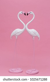 Beautiful white Flamingo model or white Flamingo bird sculpture isolated on pink background (love concept)