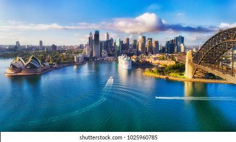 Wichtige architektonische Wahrzeichen der Stadt Sydney und Australien um den Hafen von Sydney in erhöhter Luftaufnahme in warmem, glattem Sonnenlicht am Morgen.