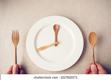 white plate with spoon and fork, Intermittent fasting concept, ketogenic diet, weight loss,  food crisis, restaurant and cafe reopening post covid-19 coronavirus pandemic