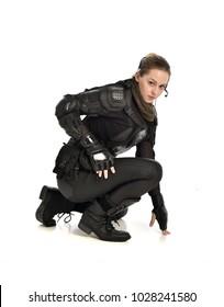Porträt in voller Länge der Frau, die schwarze taktische Rüstung trägt, hockende Haltung, lokalisiert auf weißem Studiohintergrund.