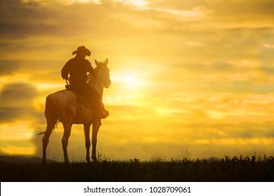 馬に乗ったシルエットのカウボーイ。牧場