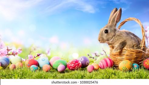飾られた卵が付いているバスケットの小さなウサギ-イースターカード