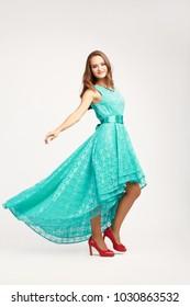 若い美しい少女モデル、ターコイズブルーのギピュールドレスを着て、赤いかかとを着て、長い髪、カメラを見て、全身、ダンスと笑顔、白い背景で隔離