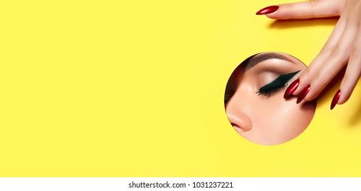 Una chica con hermosos dedos largos y uñas rojas toca el borde del ojo cerrado en el orificio circular del papel amarillo. Moda, belleza, maquillaje, cosméticos, salón de belleza, estilo, cuidado personal.