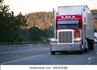 Knallroter klassischer Big-Rig-Sattelzug mit hohen Auspuffrohren und Chromzubehör, das Waren im Trockenwagenanhänger transportiert, bewegt sich auf der Abendstraße mit eingeschaltetem Scheinwerfer