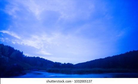 Lake at night - timelapse. Video. Night sky timelapse with running stars. A view of the stars of the Milky Way with a silhouette of a pine trees forest near a lake in the mountain. Falling stars